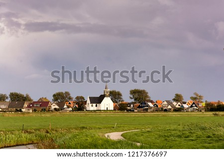 View on Oudeschild, a small historic town on the Wadden Island Texel, the Netherlands. The surroundings of the village with the white small church are rural and agricultural. The weather is rainy #1217376697