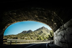 View on picturesque mountain landscape from end of a road tunnel;
