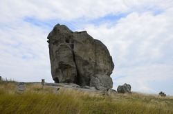 view on Pidkamin inselberg on adjacent hill and nearby ancient graveyard in Brody region of Galychyna, Ukraine. Lviv region