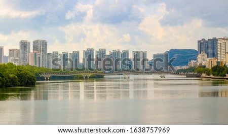 View on promenade and pedestrian bridge over the Linchun River at Sanya, Hainan island, China. A popular name among tourists is the bridge of lovers or the drunk bridge