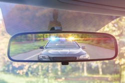 View on rear mirror of a car. Police car with lights and siren is chasing you.