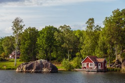 View on red holiday cabin by a lake in Stockholm archipelago, Sweden. Wooden cottage, sauna on shore. Tiny house near the water. Rocky small island, islet in water. Buildings surrounded by green trees