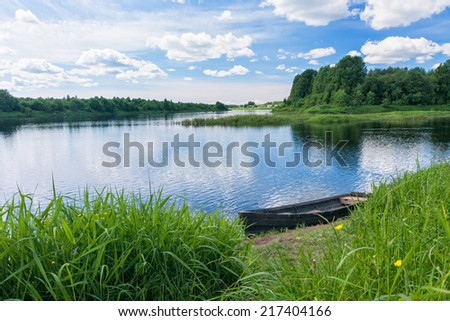 View on river with island and wooden boat laid up on riverbank. Kikovo village, Karelia, Russia.