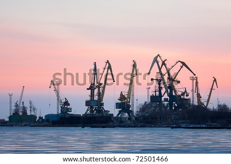 View on seaport with cranes at sunset