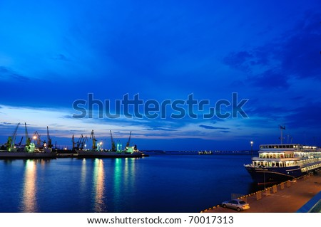 View on seaport with cranes, cargo and passenger ships at the night.