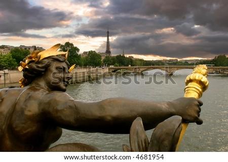 View on Seine river and Eiffel Tower through the sculpture on Alexander III bridge in Paris, France.