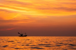 View on silhouettes of wooden pier and two boats and people relaxing and fishing in evening few moments before sunset with sun and clouds reflection sea water in summer Side,Pattaya Thailand