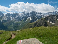 view on snow-capped moutains and green valley with winding spring stream and footpath of Stubai hiking trail, Stubai Hohenweg, Alpine landscape of Tyrol Alps, Austria. Summer blue sky