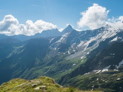 view on snow-capped moutains and green valley with winding spring stream at Stubai hiking trail, Stubai Hohenweg, Alpine landscape of Tyrol, Stubai Alps, Austria. Summer blue sky