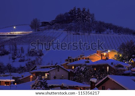 View on snowy hill with houses at evening in town of Alba in Piedmont, Northern Italy.