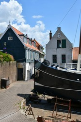View on some of the traditional houses in the fishing village of Urk in The Netherlands with in the forefront a fishing boat on a slipway for repair or maintenance