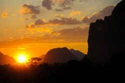 View on spectacular tropical sunset with vibrant orange yellow golden colors,  karst mountain range and hills background, sunburst effect - Laos, Vang Vieng  (focus on sky)
