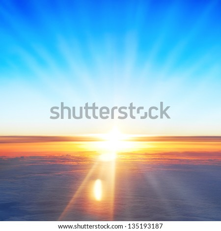 View on sun, sunset, blue sky, and ocean of clouds from airplane window.