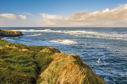 View on the Atlantic ocean. Mullaghmore peninsula, county Sligo, Ireland. Blue water with waves, cloudy sky, nobody.