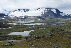 View on the beautiful landscape on the Sognefjellsvegen in summer with snow patches on the mountains and little water basins