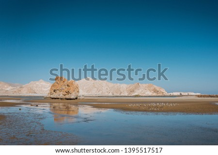 View on the big rock near Yiti beach, hills in the background, shallow water and flock of seagulls on the sand.  Photo stock ©