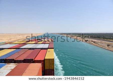 View on the containers loaded on deck of cargo ship. Vessel is transiting Suez Canal on her international trade route. Suez canal landscape. Foto stock ©