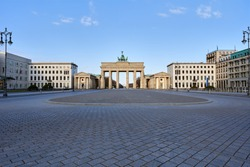view on the famous Brandenburg gate on the Pariser square in Berlin city, parisian square without tourists and visitors - deserted, blue sky, small clouds