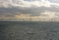 View on the London Array, offshore wind farm which is located 20 kilometres off the Kent coast in the outer Thames Estuary in the United Kingdom during winter time under overcast sky with rainy clouds