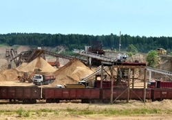 View on the mining quarry. Plant for the production sand and gravel for the construction industry. Mechanical machine, conveyor belt for crushing stone. Dump trucks transporting sand in the open-pit.
