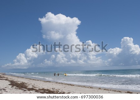 view on the ocean beach with dramatic clouds and active people in the distance