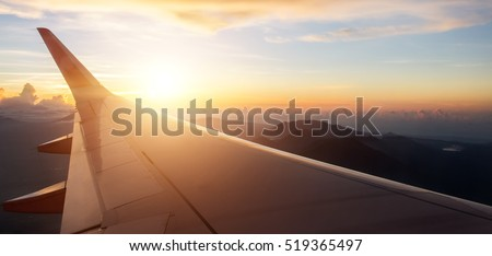View on the sunset  and airplane wing from the inside