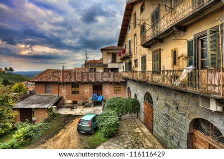 View on traditional italian courtyard among old houses under cloudy autumnal sky in town of Barolo, Italy.