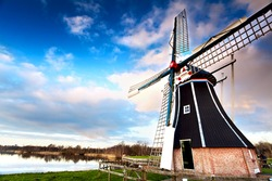 view on typical Dutch windmill over blue sky via wide angle