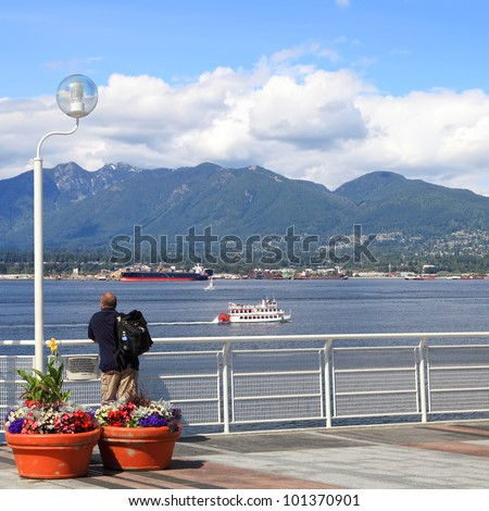View on Vancouver bay and a tourist looking at. Vancouver, British Columbia. Canada - stock photo