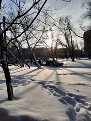 view on winterlandscape, tractor in snow, view on snowy trees, white snow, sun and clear sky,  tree shadows