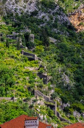 View onto the ramparts on the hillside of Saint John Mountain with ancient fortified city walls surrounding Old Town of Kotor, Montenegro