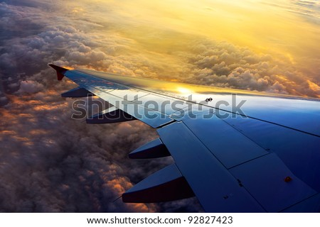 View out of airplane wing in flight Morning golden light below the clouds