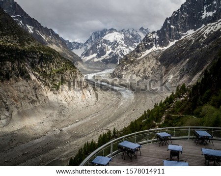 View over alpine valley, glacier and peaks of Alps in background. Empty tables of restaurant at the terrace at Mere de Glace peak. Chamonix, France