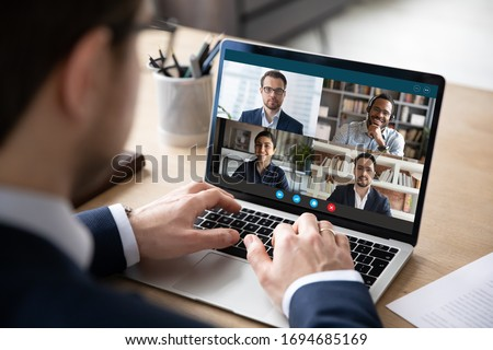 View over businessman shoulder at laptop where four multiracial colleagues engaged at group meeting on-line, video conference call communicating by webcam, distant webinar, online negotiations concept