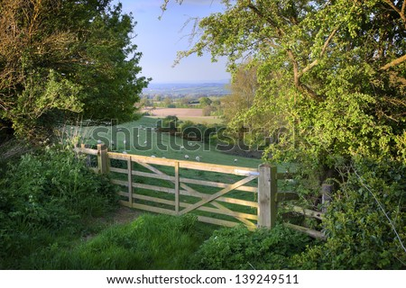 View over farm gate towards pretty English countryside