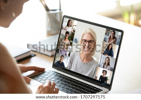 View over girl shoulder to pc screen where lot of diverse age and ethnicity women vloggers represents internet channels. Communication via modern tech, freelance, like-minded ladies friendship concept