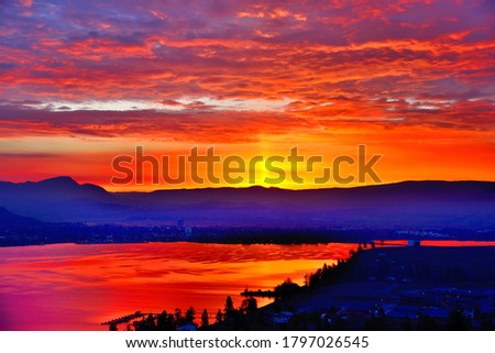 View over lake Okanagan to east shore by Kelowna BC Canada before sunrise with yellow sky, red clouds, dramatic colors reflected in the water and an old ferry dock jetty in the foreground  Foto stock ©