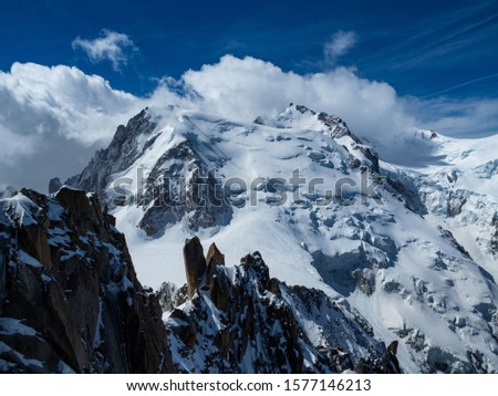 View over Mont Blanc, form the peak of Auguille du Midi. Sunny day, some clouds over Alps peaks. Chamonix, France