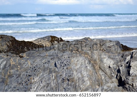 view over rocks onto waves in the distance at Fistral beach bay in Newquay Cornwall England ( rock in focus, sea blurred ) #652156897