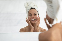 View over shoulder, beautiful woman wrapped in towel looking in mirror while applied face cream provide deeper repair, protecting facial skin. Skincare, beauty effective anti wrinkle treatment concept