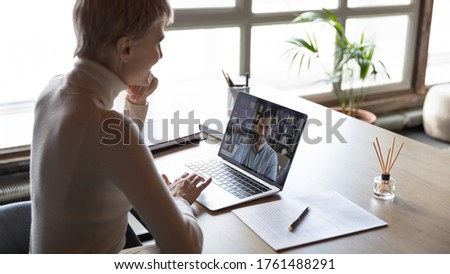 View over shoulder of HR manager looking at laptop screen listen applicant during distant online job interview. Hiring, remote negotiations, informal chat with friend at workplace, video event concept