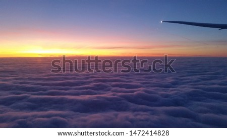 View over sunset over the clouds in an airplane