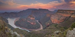 View over the Blyde River Canyon and the Three Rondavels in South Africa at sunset.
