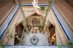 View over the courtyard of a traditional Moroccan Riad from the top floor, with stucco details, colorful tiles and indoor plants