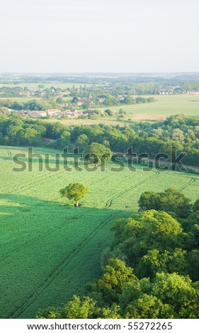 view over the early summer green fields and a small village from the air; East Anglia; UK
