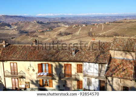 View over the house roof on hills of Piedmont and Alps with snowy peaks on the background in Northern Italy.