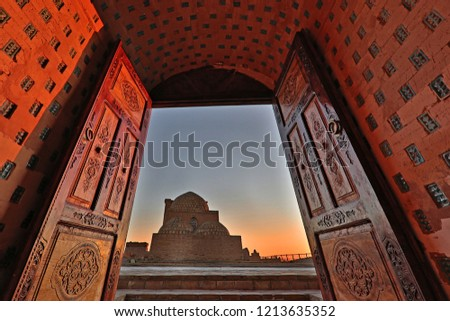 View over the mausolem through wooden doors at the sunset, in the ancient cemetery of Mizdakhan in Nukus, Uzbekistan
