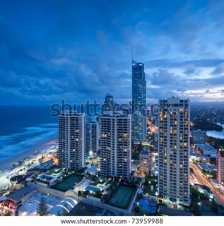 view over the modern city at dusk with ocean beside on square format (gold coast,queensland,australia)