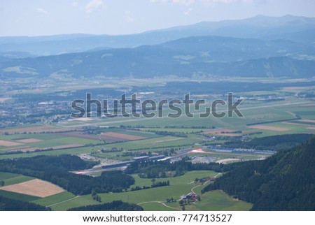 Stock Photo View over the Styrian Murtal and the surrounding mountains. Formula1 and MotoGP racetrack Red Bull racing course in Spielberg seen from above on Tremmelberg.