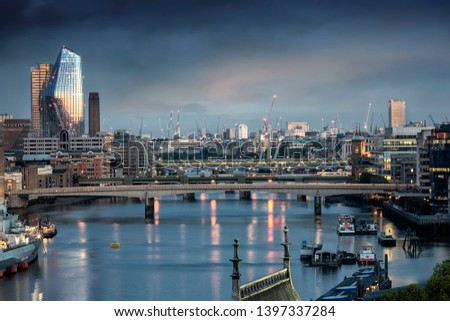 View over the Thames river to the skyline of London, UK, with the various bridges and construction cranes during morning dawn